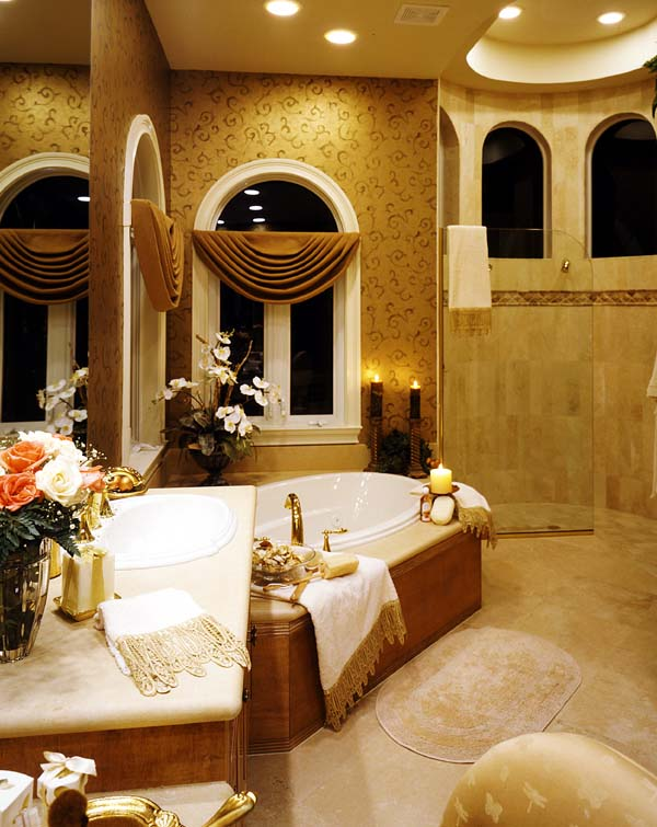 The opulent master bath includes an elegant soaking tub and curved-wall walk-in shower.