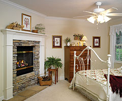 The second level master bedroom receives added warmth from a romantic fireplace.