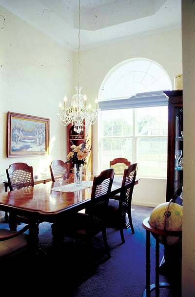 A soaring ceiling and round topped window enhance the formal dining room's sense of elegance.